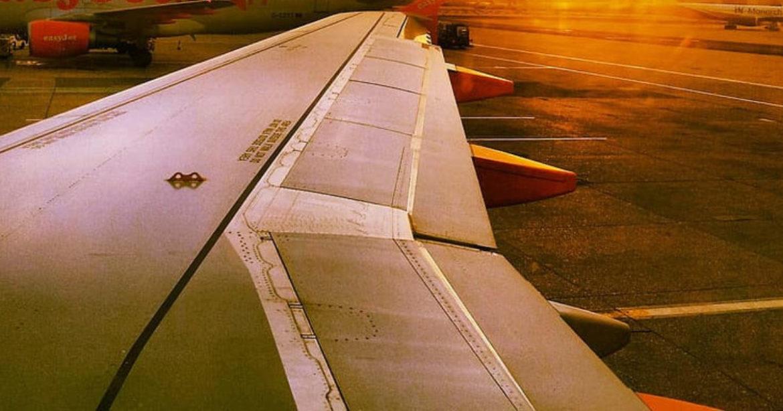 woman walks airplane wing